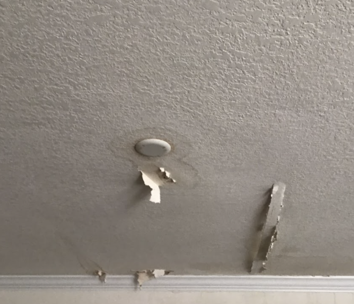 a ceiling with discoloration around a light fixture