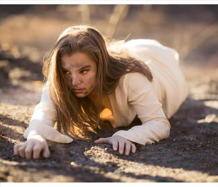 Young mixed race woman in white dress crawls on ground by trees destroyed by wildfire while covered in ashes